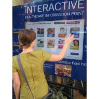 En kvinde, der bruger et 32 tommers touchscreen overlay vindue