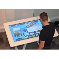 Ein Mann, der eine interaktive Tabelle des Touchscreens verwendet