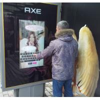 Ein Mann mit einem 32-Zoll-Touchscreen-Overlay-Display an einer Bushaltestelle