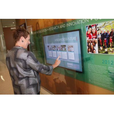 Eine Frau, die einen projizierten kapazitiven Touchfilmschirm verwendet
