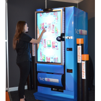 A woman using a vending machine with a thick glass touch screen