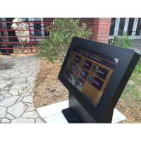 An outdoor touch screen kiosk with a cow in the background