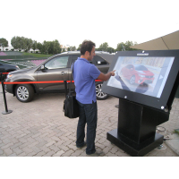 A man using an outdoor kiosk with a thick glass touch screen