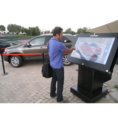 A man using a 55 inch touch screen overlay kiosk