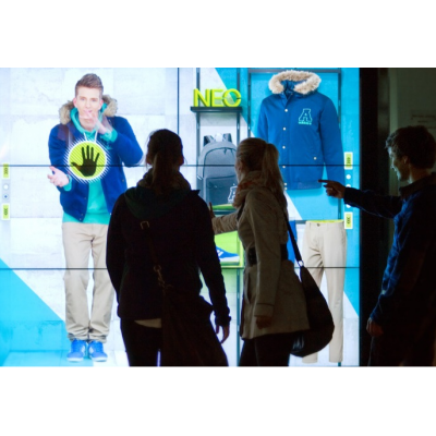 A couple using a large format touch screen display shop window