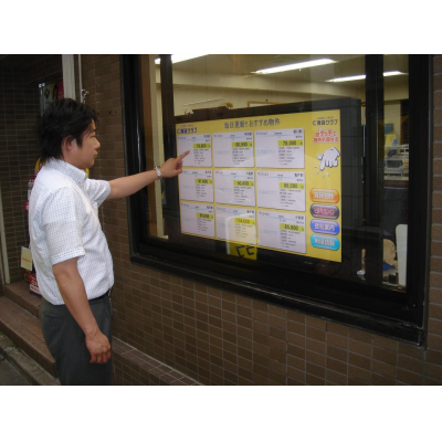 A man using a 40 inch touch screen overlay shop window display