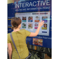 A woman using a through-window self service touch screen kiosk