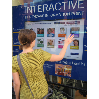 A woman using a 32 inch touch screen overlay window