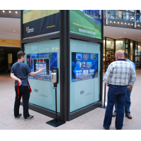 People using an interactive wayfinding kiosk in a shopping centre
