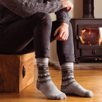 A man wearing HeatHolders warm socks in front of a fire.