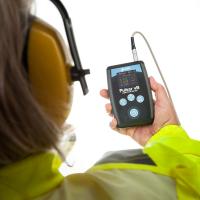 An industrial worker using a hand-arm vibration meter from Pulsar Instruments.