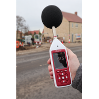 Decibel meter being used for vehicle noise measurement.