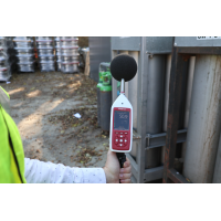 Environmental noise decibel meter being used for industrial noise assessment.
