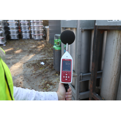 Bluetooth sound level meter being used for industrial acoustic measurement.