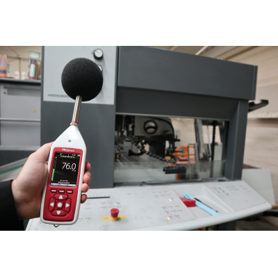 Bluetooth decibel meter being used for industrial noise assessment.