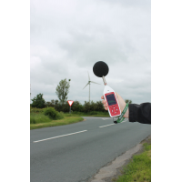 An Optimus environmental and occupational noise measurement device being used outside by a road.