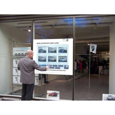 Papel multi-touch usado por un hombre en un concesionario de automóviles