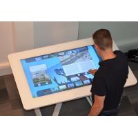 Un hombre que usa una mesa interactiva de cristal táctil