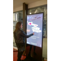 Una mujer que usa un tótem de pantalla táctil de PCAP