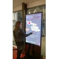 Una mujer que usa un tótem de pantalla táctil profesional