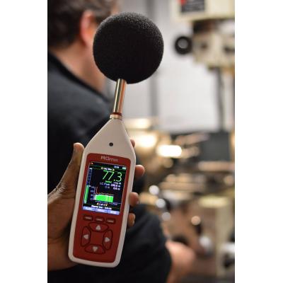 el equipo de monitoreo de ruido del lugar de trabajo en una fábrica de tomar una lectura
