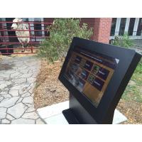 Un kiosque d'écran tactile en plein air avec une vache en arrière-plan