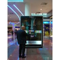 एक शॉपिंग सेंटर में अनुमानित कैपेसिटिव टच स्क्रीन का उपयोग करने वाला एक आदमी।