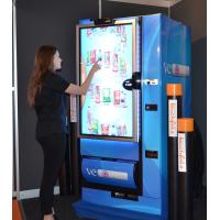 एक मोटी ग्लास टच स्क्रीन के साथ एक वेंडिंग मशीन का उपयोग कर एक महिला