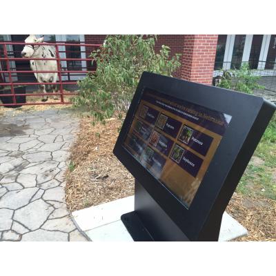 पृष्ठभूमि में एक गाय के साथ एक आउटडोर टच स्क्रीन कियोस्क