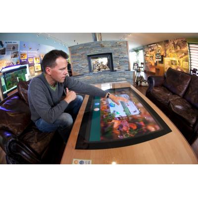 एक आदमी द्वारा उपयोग किए जाने वाले टेबलटॉप ग्लास पर लागू संवेदनशील फिल्म को स्पर्श करें