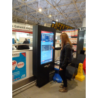एक हवाई अड्डे पर एक टच स्क्रीन टिकट मशीन समय सारिणी का उपयोग कर एक लड़की