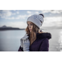 Seorang wanita mengenakan topi dan sarung tangan dari HeatHolders: pemasok pakaian termal terkemuka.