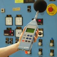 Seorang pekerja menggunakan alat pengukur kebisingan profesional.