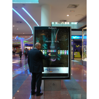 Een man met een geprojecteerd capacitief aanraakscherm in een winkelcentrum.