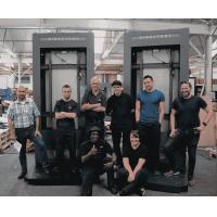 Armagards medewerkers van de digital signage-fabrikant buiten met voltooide totems.