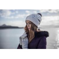 En kvinna som bär hatt och handskar från HeatHolders: den ledande leverantören av termiska kläder.